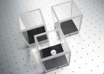 Három darab kisméretű, kocka alakú plexidisplay egy munkaasztalon.
