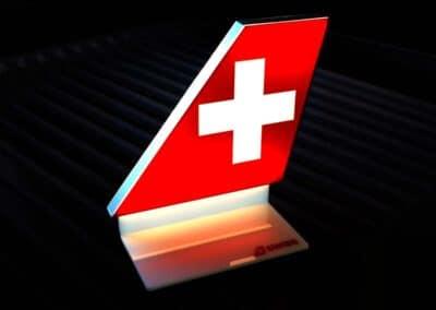 Prémium minőségű, világító asztali display a légitársaság vörös alapon fehér keresztet formázó logójával sötét háttér előtt.