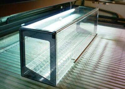 Frissen elkészült, nagyméretű, felnyitható elejű plexi cigarettatartó display pihen egy kivágógép munkatálcáján.