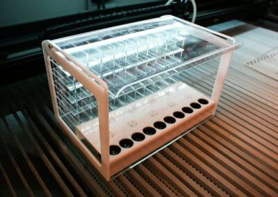 Kisméretű plexi szivartartó display hever egy kivágógép fémtálcáján.