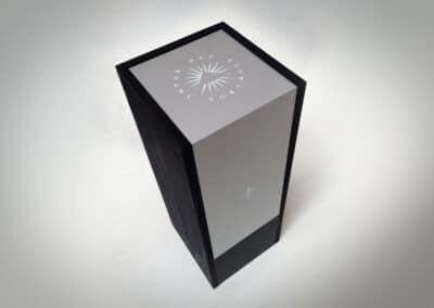 Exkluzív bortartó feketére festett fából é s fémből. A tetején világító Impar Nec Pluralbus felirattal az oldalán elegáns logóval