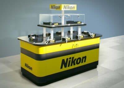 Kulccsal nyitható, masszív sárga-fekete Nikon showcase tároló résszel, plexi vitrinnel, lopásgátlóval szerelt terméktartókkal és egy extra koronával a cég logója számára.