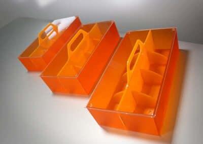 Három darab, narancsszínű füles, rekeszes tároló egy fehér asztalon.